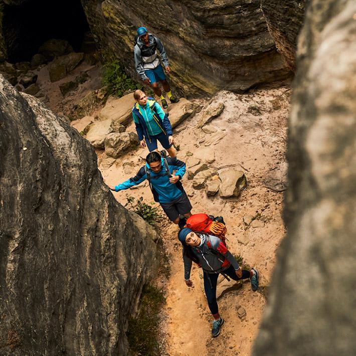 Four hikers walk between rocks